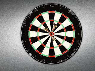 A dartboard with three darts in bullseye
