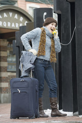 Young woman on the phone with suitcase