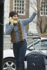 Young woman waving while on phone