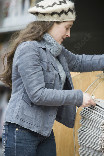 Young woman looking at newspapers