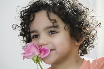 Pretty child smelling a flower