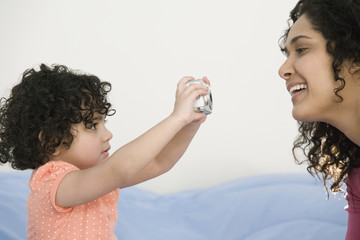 Hispanic child taking picture of mother