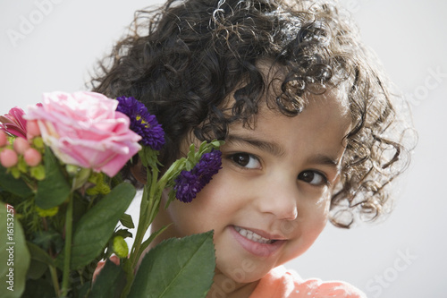 Cute Hispanic child with flowers