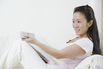 Asian woman using a remote