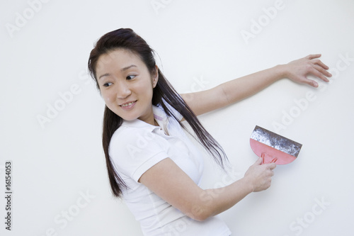 Asian woman scraping for paint
