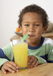 Young boy in kitchen drinking glass of fruit juice smiling