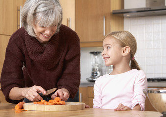 Woman and young girl in kitchen slicing carrots and smiling