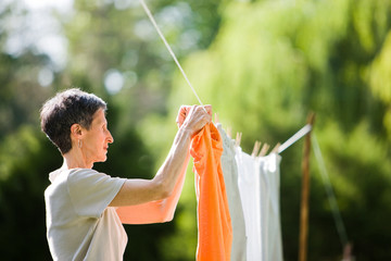 Woman Hanging Orange Shirt on a Clothesline