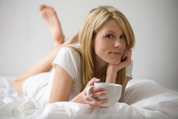 Woman Reclining on Bed With Coffee Cup