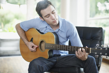 Man sitting in living room playing acoustic guitar