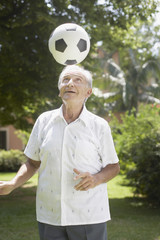 Senior man outdoors balancing soccer ball on head