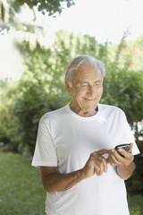 Senior man outdoors using a personal digital assistant and smiling