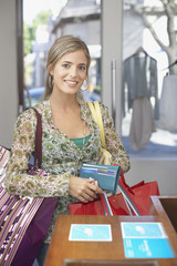 Woman in store holding wallet and shopping bags smiling