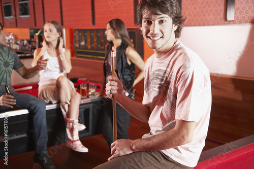 Man sitting on pool table smiling and holding pool cue