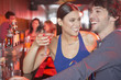 Couple in nightclub at bar with beverages smiling