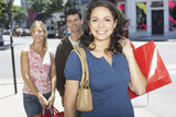 Woman outdoors with shopping bags smiling