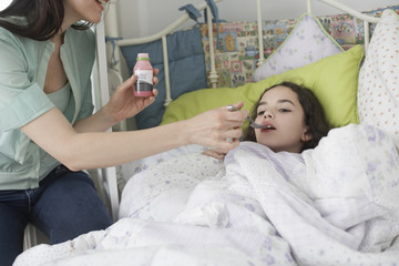 Woman helping young girl take medicine in bedroom