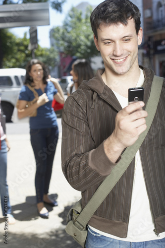Man outdoors using cellular phone and smiling