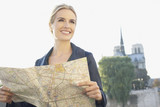 Woman outdoors holding map and smiling