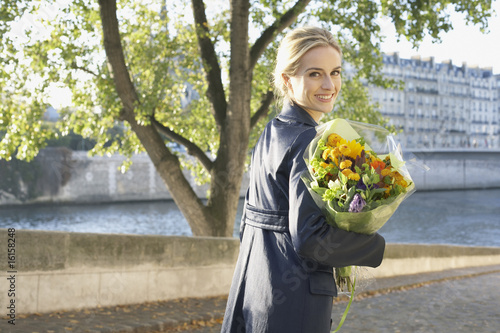 Woman outdoors carrying flowers and smiling