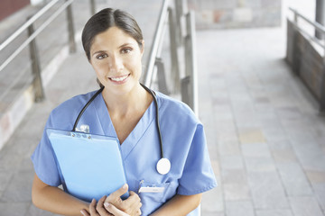 Hospital worker standing outside hospital holding clipboard and smiling