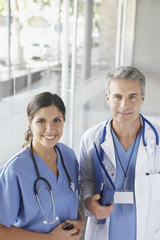 Two hospital workers standing in corridor holding cellular phone and smiling