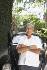 Senior man standing outdoors by car smiling