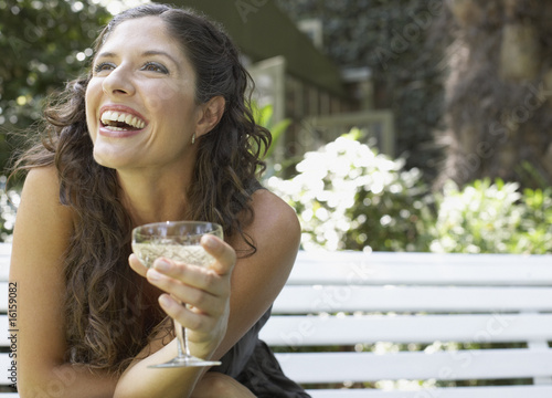 Woman sitting outdoors on bench with white wine smiling