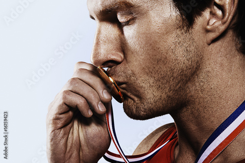 Athete kissing gold medal