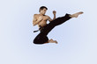 Man practicing martial arts and jumping in the air