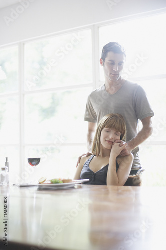 Woman sitting at dinner table smiling with man standing holding her hand