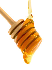 Honey flowing over wooden dipper