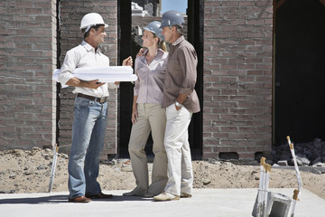 Couple talking with foreman on construction site