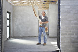 Construction worker lifting lumber on construction site