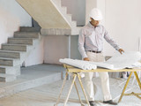 Construction foreman reviewing blueprints at construction site