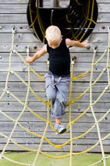 Little boy climbing in the ropes