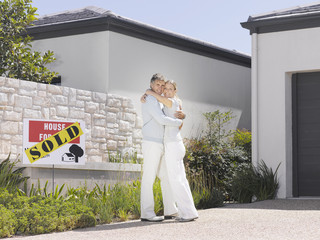 Couple hugging in driveway of new home