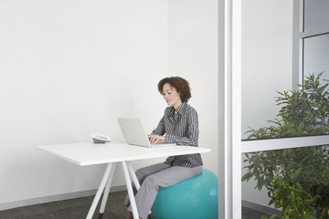 Businesswoman sitting on exercise ball in office