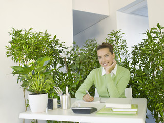 Businesswoman working at desk surrounded by plants