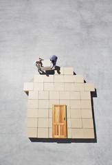 Couple building house outline on sidewalk