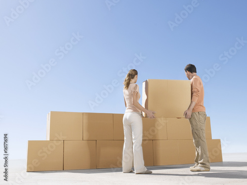 Couple stacking boxes in desert