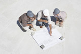 Architect viewing blueprints with home owners