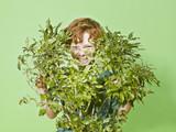 Young boy hiding behind green bush