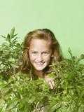 Young girl hiding behind green bush