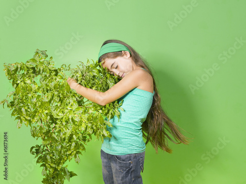 Young girl hugging green bush