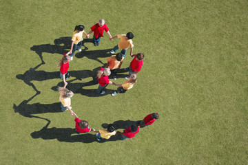 Group of children holding hands in spiral formation