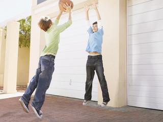 Two young boys playing basketball