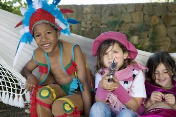 Three children in costumes sitting in hammock
