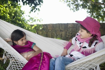 Two young girls in costume sitting in hammock