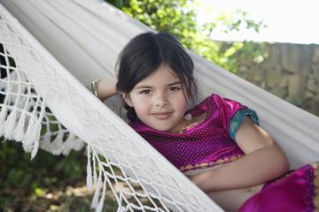 Young girl in costume sitting in hammock